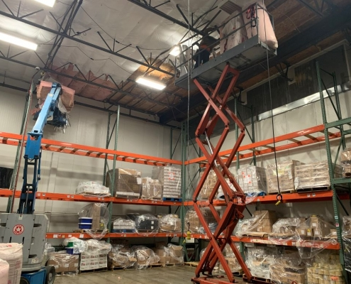 High ceiling Commercial warehouse interior where fiberglass Insulation Batts are being installed using a vertical scissor lift. Commercial Insulation Services, batt insulation