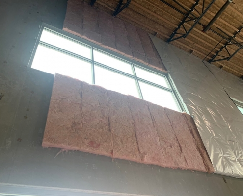 High ceiling Commercial warehouse interior where fiberglass Insulation Batts are being installed on walls using stick pins. Commercial Insulation Services, batt insulation