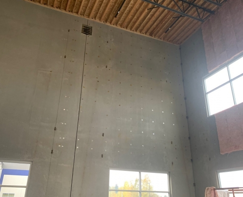 Gray concrete wall of interior high ceiling commercial building showing stick pins used to install the pink fiberglass batts insulation to save energy