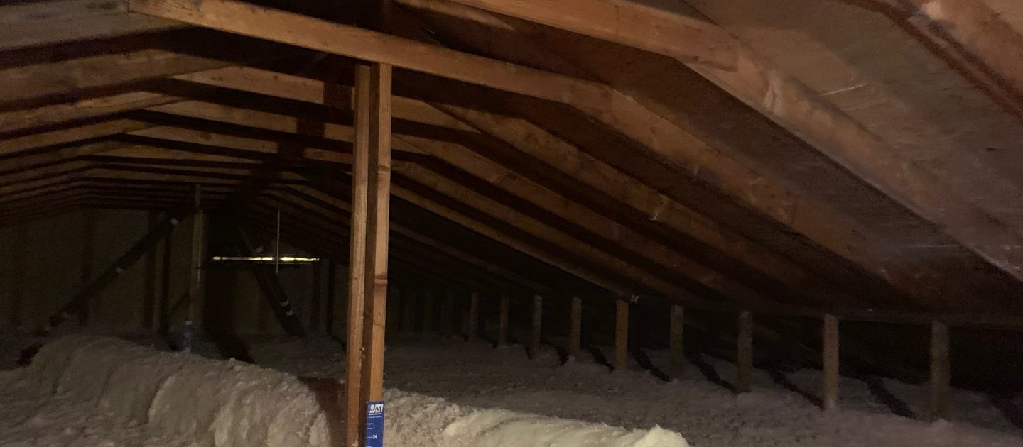 Old House Attic with beams, trusses and exhaust pipes exposed. New blow-in insulation installed, cellulose insulation, residential insulation