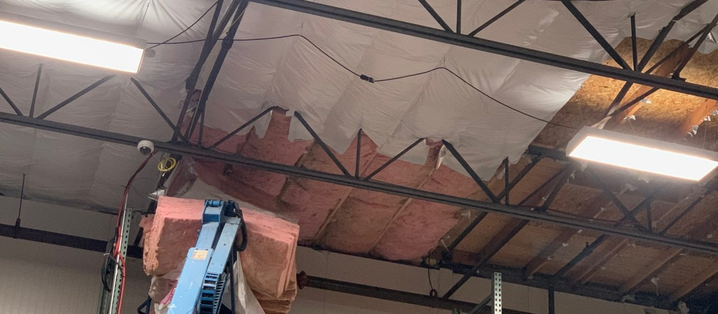 High ceiling Commercial warehouse interior where fiberglass Insulation Batts withy FSK Foil paper for mold prevention are being installed using a vertical scissor lift. Commercial Insulation Services, batt insulation