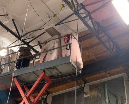 High ceiling Commercial refrigerated warehouse interior where R30 High Density fiberglass Insulation Batts with WMP-VR-R Plus barrier are being installed using a vertical scissor lift. Commercial Insulation Services, batt insulation