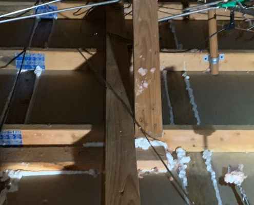 Attic space showing a ceiling of an Old house ceiling where the old damaged insulation have been removed to properly Air sealing around a plumbing PVC pipes, plastic electrical boxes to fill gaps, cracks or holes to avoid air to leak into the house. Air sealing , Attic Insulation,Residential Insulation
