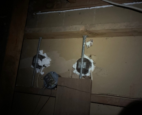 a view fron the attic showing the electrical boxes attached to the drywall ceiling being airsealed, insulation removal, air seal, blow-in insulation
