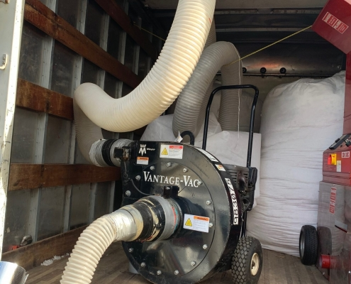 Inside of a Box Truck with Vantage-Vac brand Insulation Removal equipment with big white fabric bags to collect the removed insulation, insulation removal, blow-in insulation